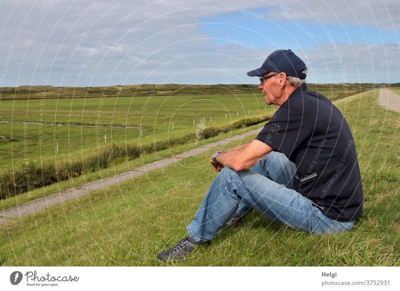 Break - male senior sits at the dike and looks at the meadows Human being Man Senior citizen age 60 years and older Male senior 1 portrait Adults Exterior shot
