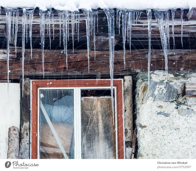 Long icicles hang from the roof of an old hut. Detail view with red window frame, stones and wooden beams Icicle Frost Window Winter Winter mood Ice Stone wall