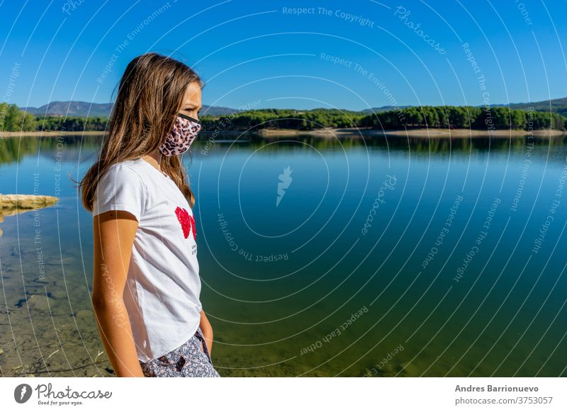 Girl with a white t-shirt and a mask to protecet herself from the coronavirus posing in a lake with the forest reflected in the water cute young caucasian joy