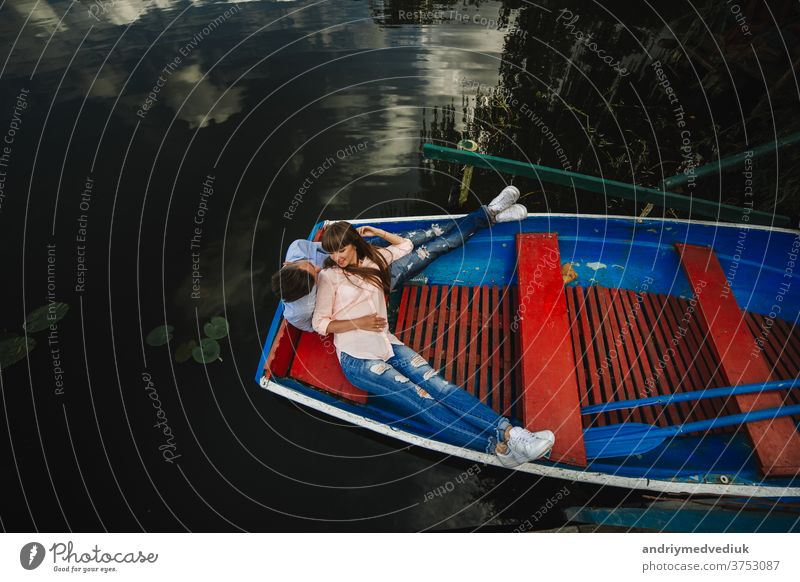 Loving couple in boat. Top view of beautiful young couple embracing and smiling while lying in the boat. love water lake travel two people adventure