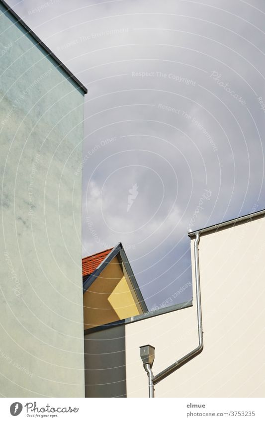 Mix of shapes and lines of differently coloured house walls with gutter and downpipe against a cloudy sky, casting shadows House (Residential Structure) Colour