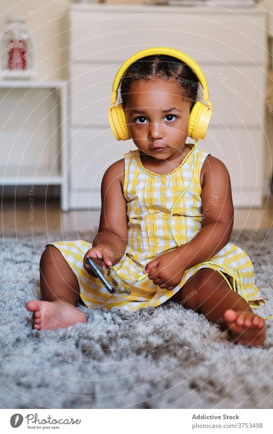 Cute little child in headphones at home listen music enjoy curious song girl black ethnic african american dress kid cute audio sound childhood rest melody sit