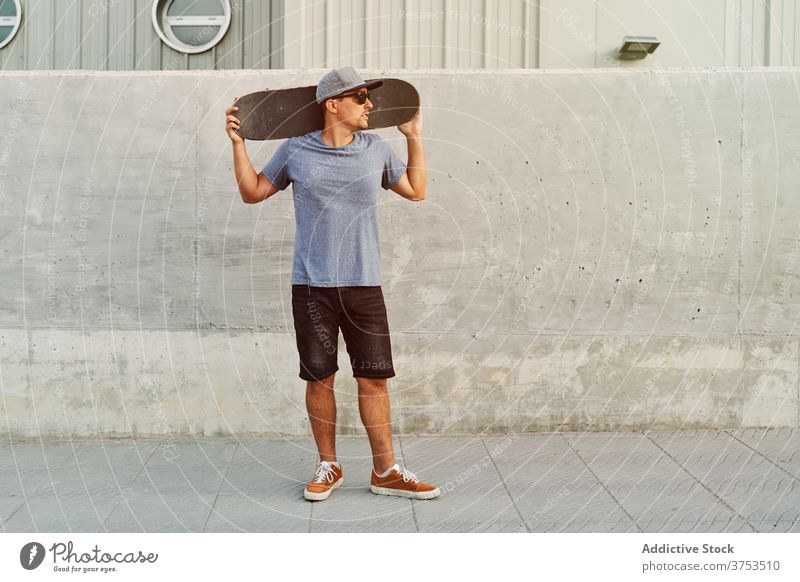 Confident man with skateboard near building city skater determine style hobby trendy urban street male sunglasses outfit modern stand cool young hipster