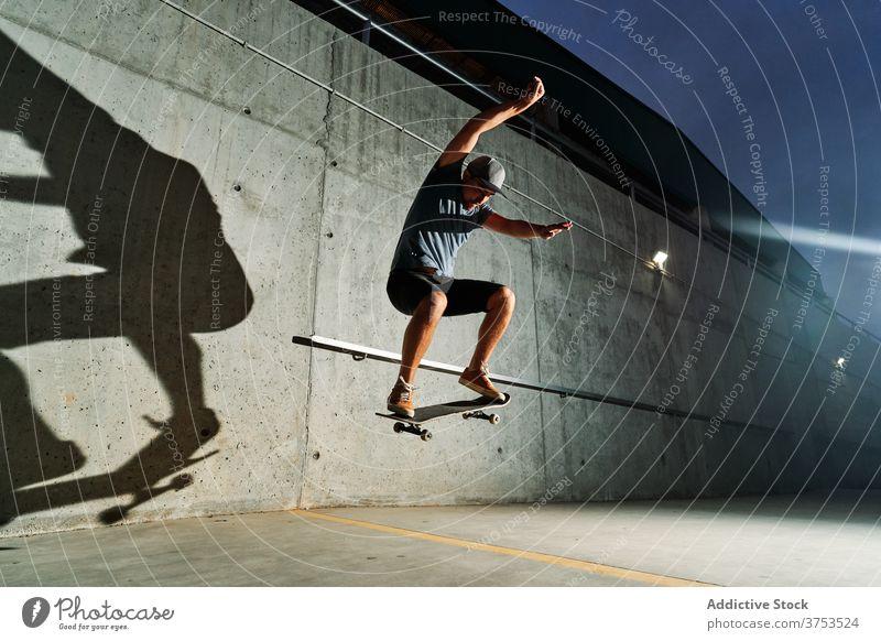 Strong man doing tricks on skateboard skater jump stunt urban skate park night skill male training sport talent practice street action energy city guy determine