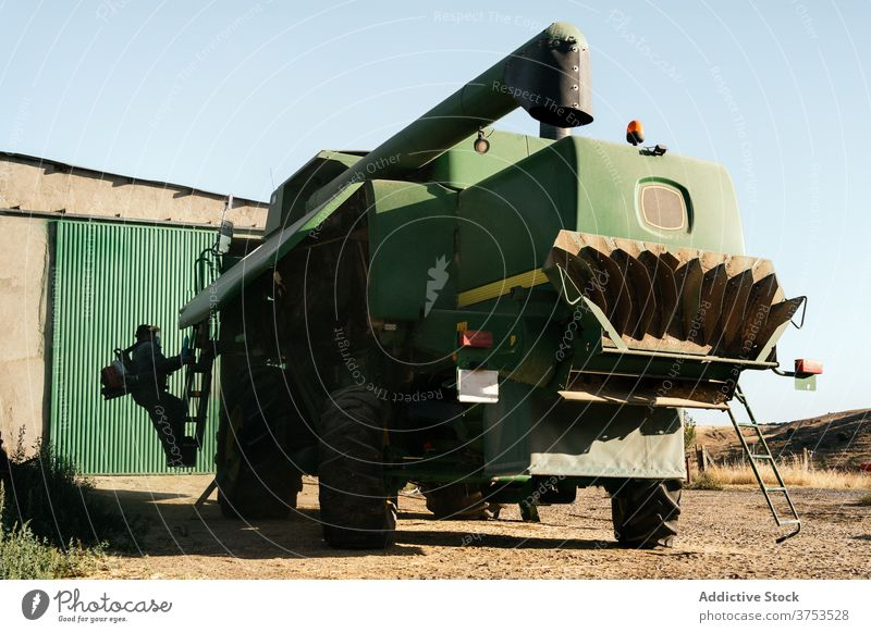 Agricultural machine parked in farm yard harvester combine agriculture vehicle farmland transport machinery car mechanism maintenance season countryside rural