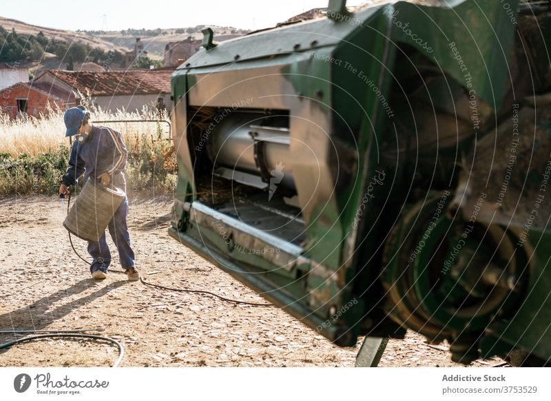 Farmer repairing detail of agricultural machine farmer harvester combine agriculture vehicle maintenance filter hydraulic farmland transport machinery car