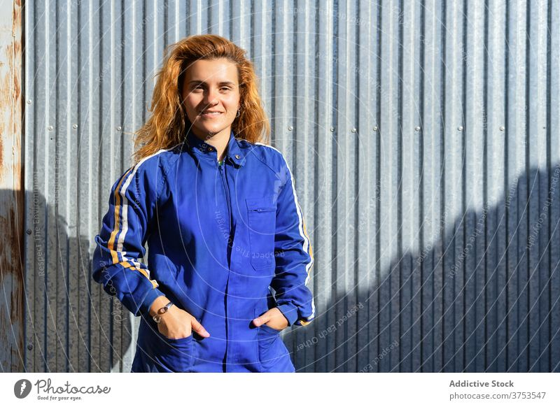 Content female worker in uniform near factory industrial woman employee break smile glasses plant workwear job metal wall professional joy rest confident lady