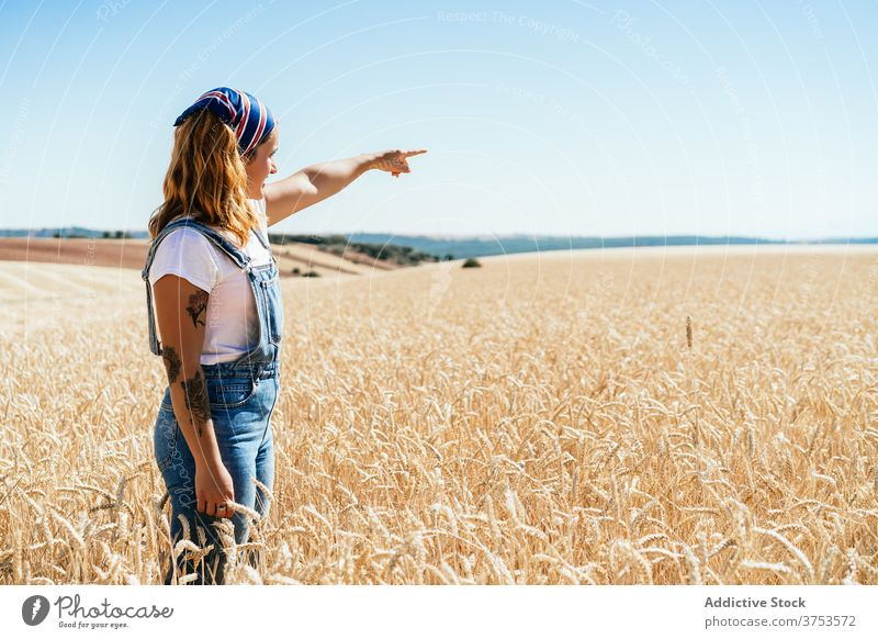 Woman in golden field in summer wheat woman countryside farmer agriculture nature rural female denim overall meadow freedom stand farmland harvest carefree