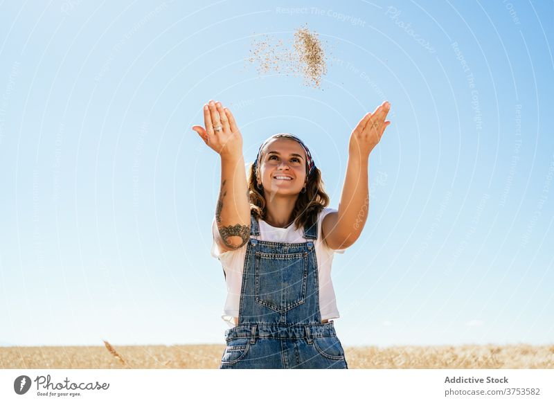 Cheerful woman with wheat grain in field countryside village agriculture toss cheerful cereal female summer meadow idyllic season cultivate sunny plant happy