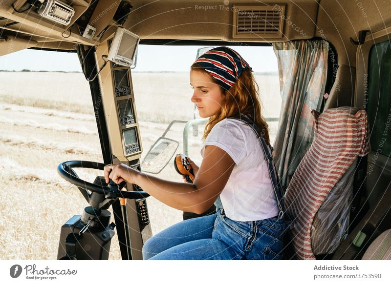 Focused woman operating agricultural machine farm combine harvest operate collect season field agriculture female wheat rural job transport vehicle equipment