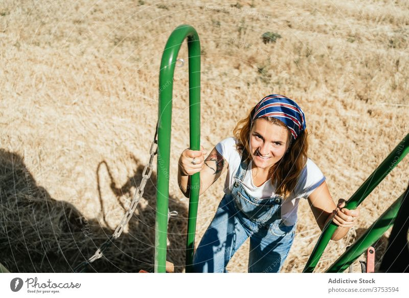 Woman on steps of combine harvester machine woman field farmer wheat countryside transport female summer nature agriculture rural season plant work growth