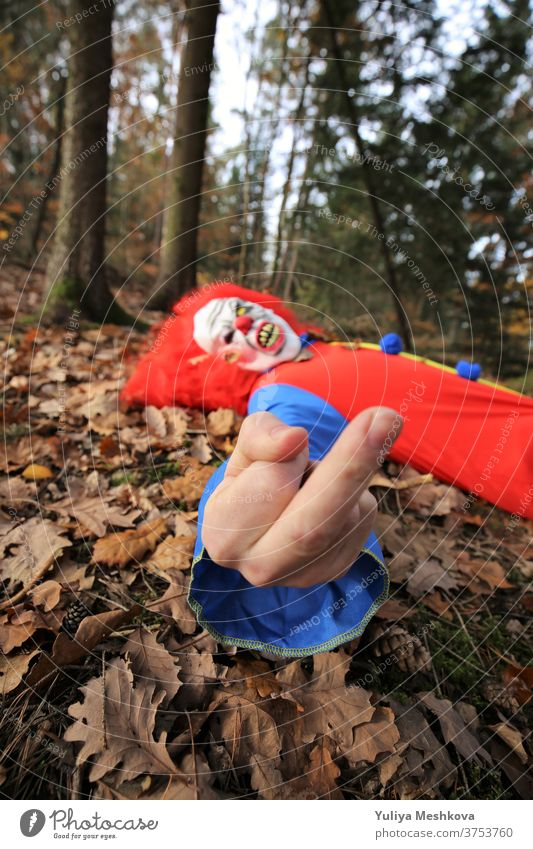 Halloween party. Fuck you. The evil clown gives the finger. Mittle finger gesture. Hallowe'en Party Clown Creepy costume clown overalls Red hair Autumn Forest