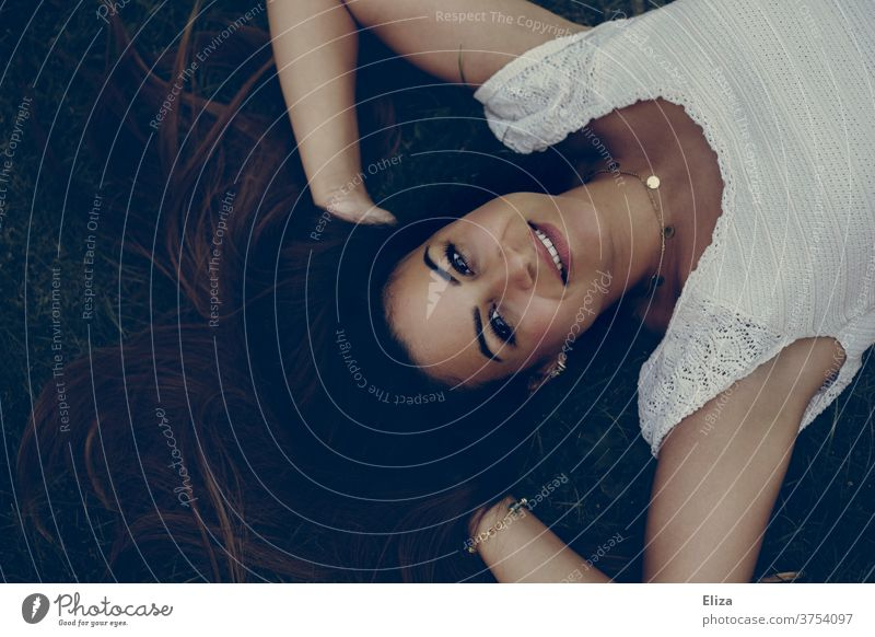 Young dark-haired woman lies on the floor with her hands in her hair and looks radiantly upwards into the camera Young woman Dark-haired brown-haired