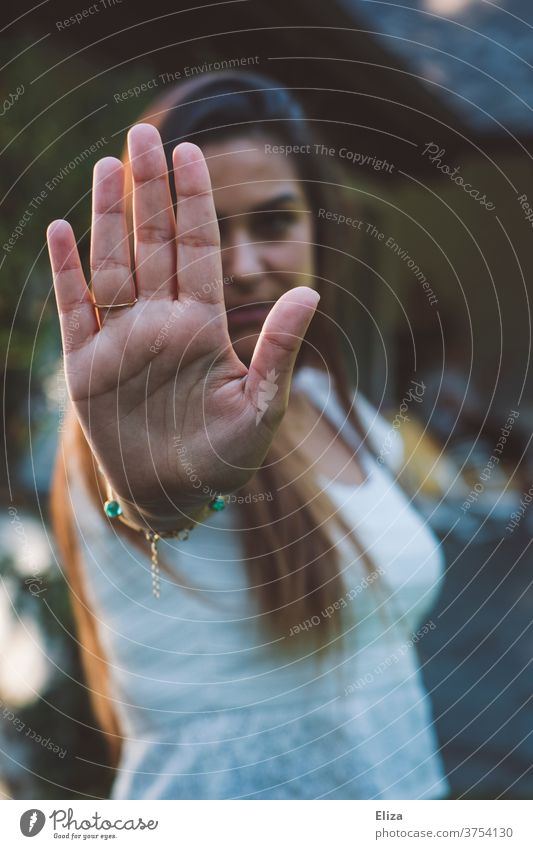 A young woman symbolizes stop by stretching out her hand in front of her. No means no. holds Woman Young woman no means no Defensive Cancelation Emotions Signal