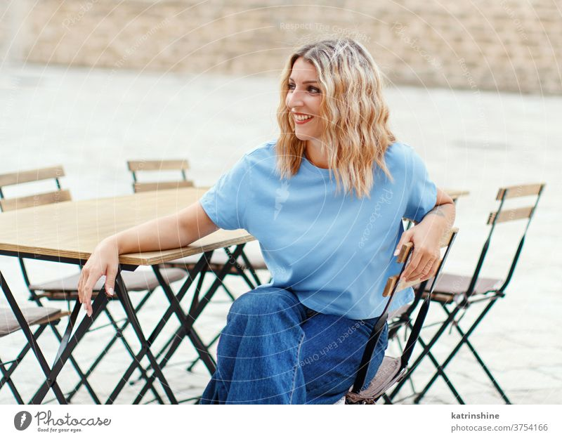 Young women wearing t-shirt and jeans sits in a street cafe girl mockup table round neck apparelmockup casual mock up Seat Person Outdoor Sitting City Portrait