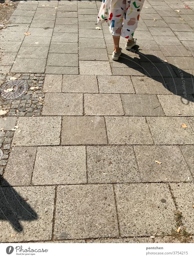 Legs of a woman in a white culotte with colorful geometric shapes on a cobbled pavement. Casting shadows. Walking, pedestrian Fashion garments Geometry