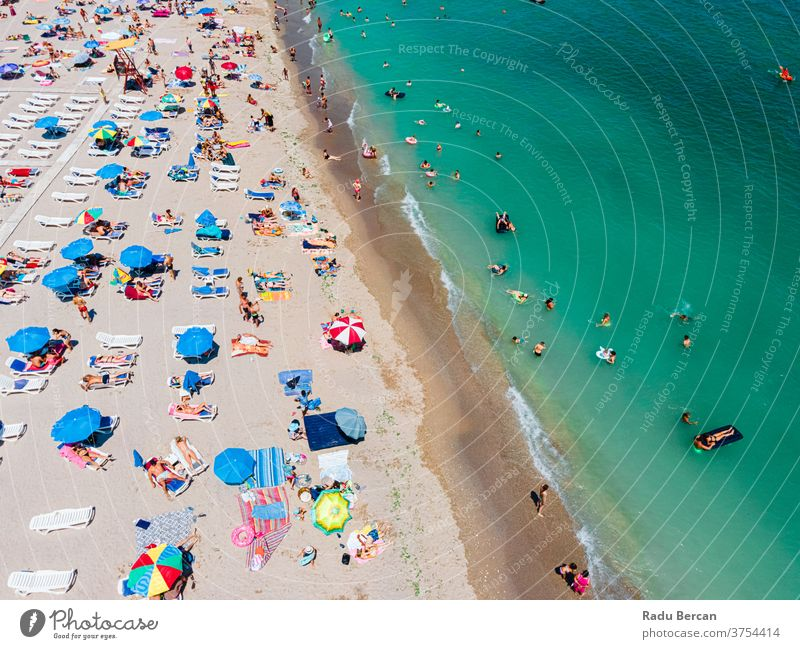 Aerial View Of People And Colorful Umbrellas On Ocean Seaside Beach In Summer beach aerial view sand background water sea vacation blue travel people