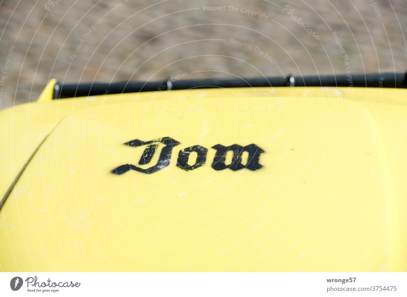 Lid of a yellow drum with the inscription Dom ton yellow ton dustbin lid Dome Inscription label Trash Exterior shot Colour photo Recycling