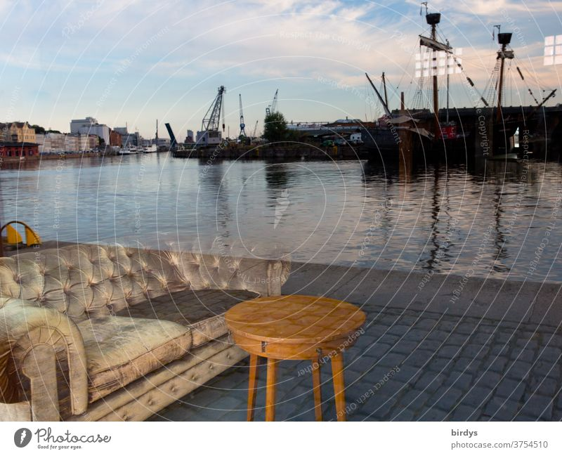 A sofa with a table stands at the quay of the port of Lübeck. Deceptive reflection in a window pane Harbour Sofa Table Reflection ships cranes port facility