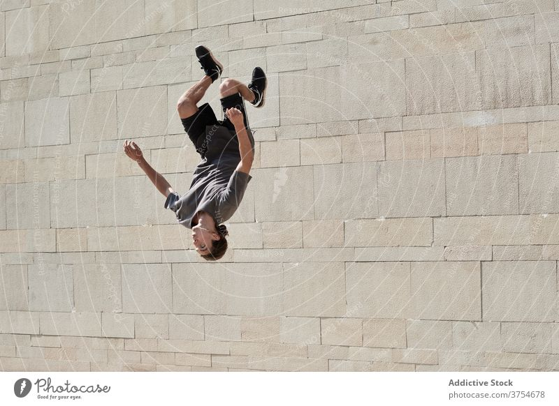 Man doing back flip in city parkour man somersault jump acrobatic stunt trick urban active male energy summer practice exercise upside down above ground