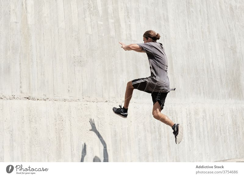 Strong man jumping on wall of building parkour stunt freestyle trick urban city extreme danger male street courage young active handsome activity professional