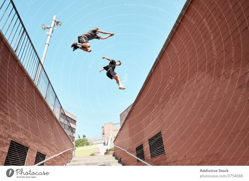 Men jumping over stairway in city parkour stunt trick men together urban extreme danger hobby courage active activity professional brave adrenalin cool energy