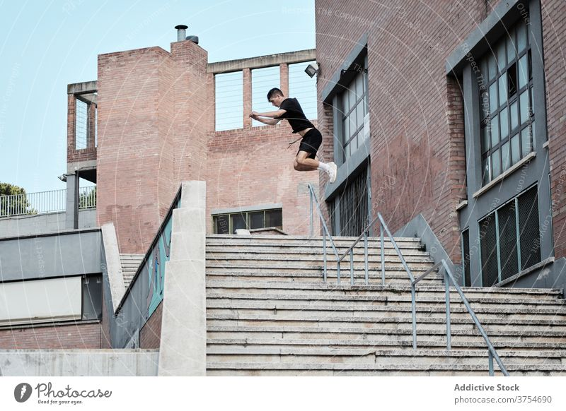 Man doing parkour in city jump stunt man stair trick urban adrenalin extreme male hobby danger courage active activity professional brave energy skill