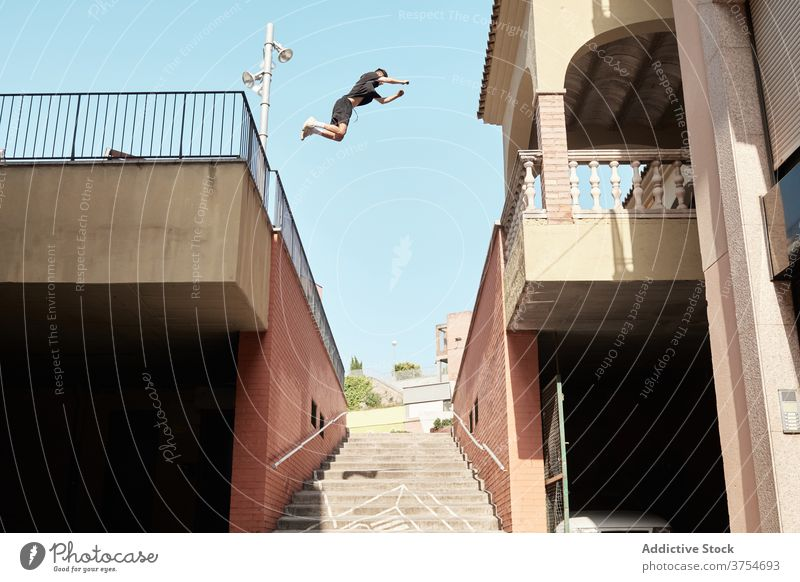Man jumping over stairway in city parkour stunt trick man urban extreme danger hobby courage active activity professional brave adrenalin cool energy skill