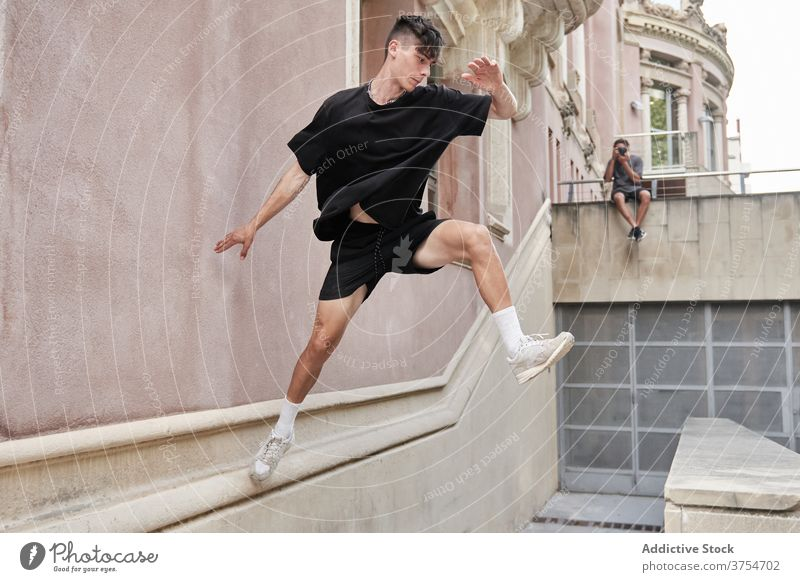 Strong man doing parkour on street jump obstacle stunt trick balance urban adrenalin extreme male city hobby courage active freestyle activity professional