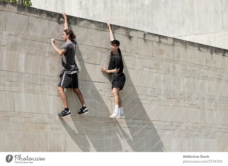 Strong men hanging on wall of building parkour freestyle risk stunt urban together extreme trick city danger courage young active handsome activity professional