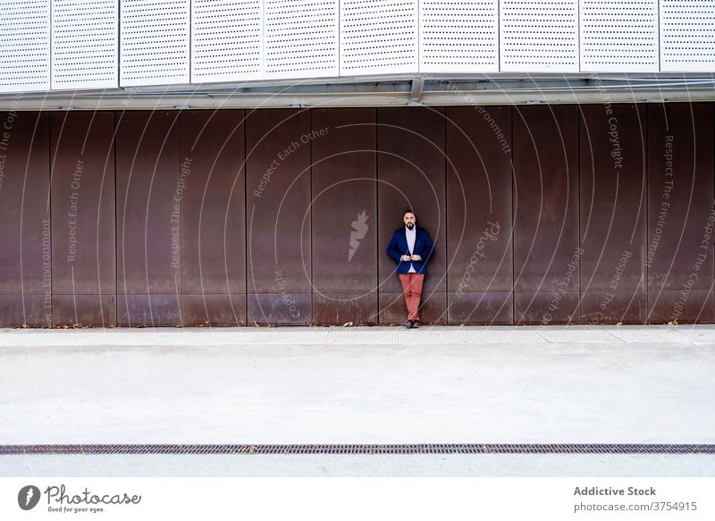 Bearded man in blue jacket leaning on metallic wall business beard male standing adult looking lifestyle businessman people person technology photogenic young