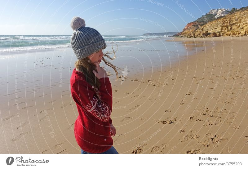 Girl in a bobble hat on the beach in Portugal in winter shore kid fun joy happy caucasian person outdoor travel lifestyle vacation water beautiful algarve alone