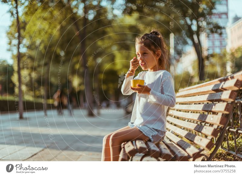 Hispanic kid sitting on a park bench with beautiful trees in the background. She is eating an ice cream. outside real happy sunset season natural seasonal fun