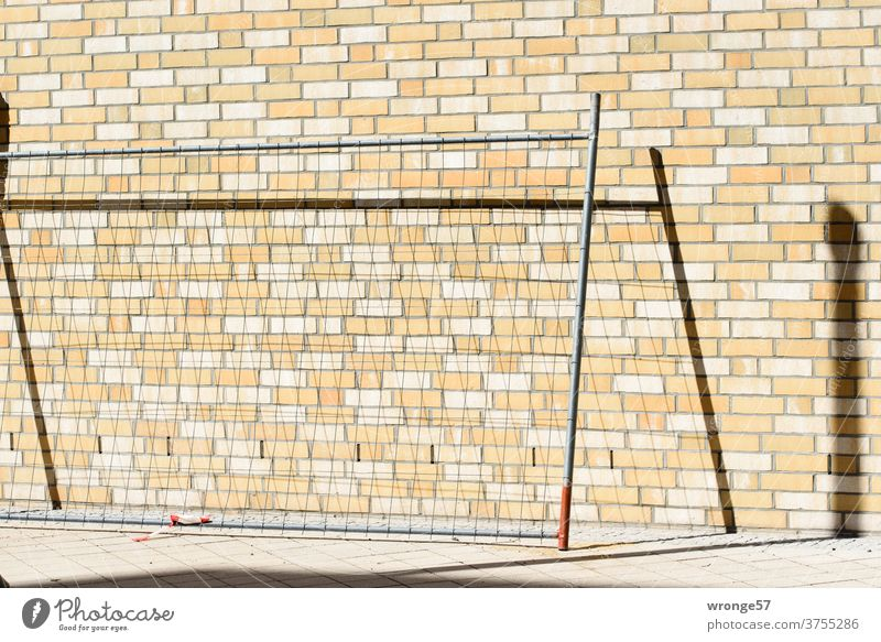 A field of a building fence leans against a wall of clinker bricks and draws a shadow on it Fence Hoarding Construction site Fence field Safety cordon