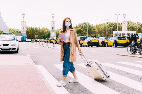 young woman with a face mask crosses the street to take a cab out of the train station coronavirus tourism transportation tourist public journey trip commuter