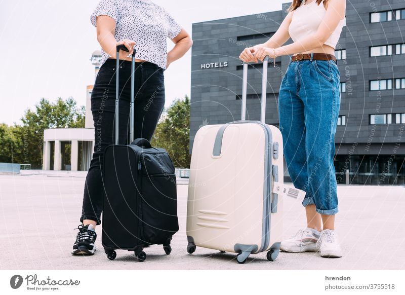 two unrecognizable tourists with their bags in front of the hotel where they are going to stay luggage hotels hostage tourism vacations transport public journey