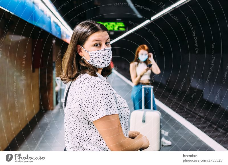 young woman with a face mask waiting for the subway transportation public journey tourist trip commuter train traveling voyage economy virus coronavirus