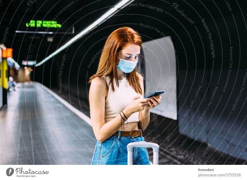 young woman with face mask checks her smartphone while waiting for the subway transportation public journey tourist trip commuter train traveling voyage economy