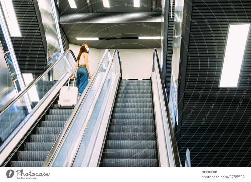 young tourist with face mask uses subway escalator stairway terminal coronavirus tourism transportation public journey trip commuter train staircase traveling
