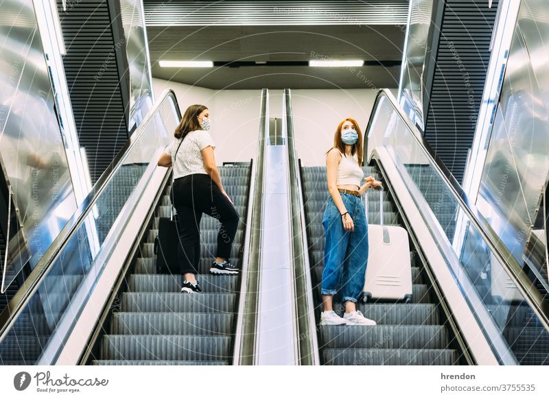 two young tourists wearing face masks use the subway escalators stairway terminal coronavirus tourism transportation public journey trip commute train staircase
