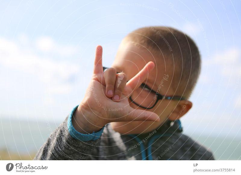 boy making horn sign Rock music Hand hand gesture Sign Culture Fingers Thumb Little finger index finger Hinduism bad luck evil eye Superstition Reaction insult