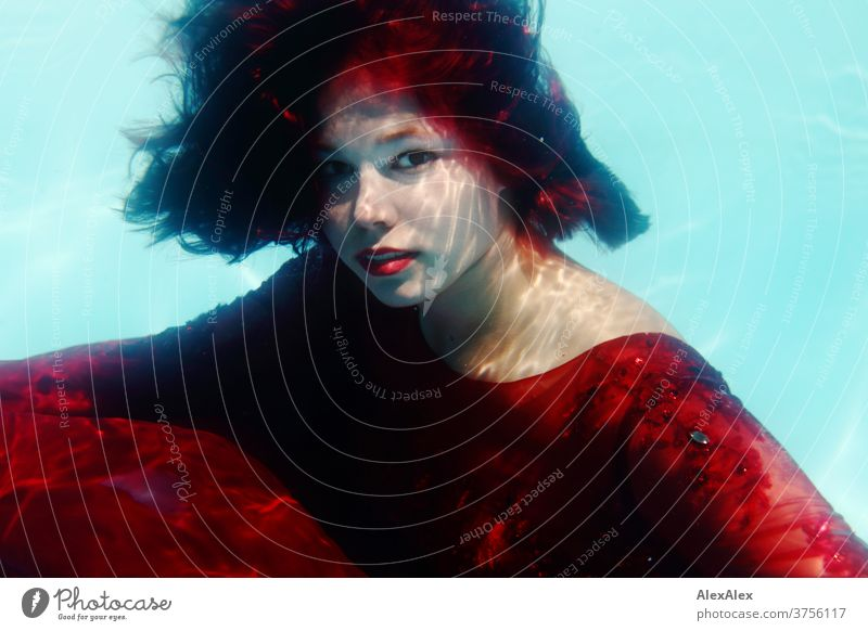 Young woman in red ball gown dives in a swimming pool Woman girl already daintily Athletic Sunlight Summer swimming pools Water Aquatics Desirable Adults