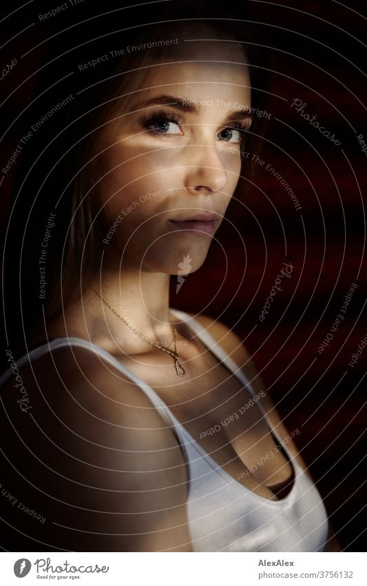 Dark portrait of a young woman with light stiffeners through the blinds Day Aesthetics focused Force décolleté great Definitive Calm athletic Skin Uniqueness
