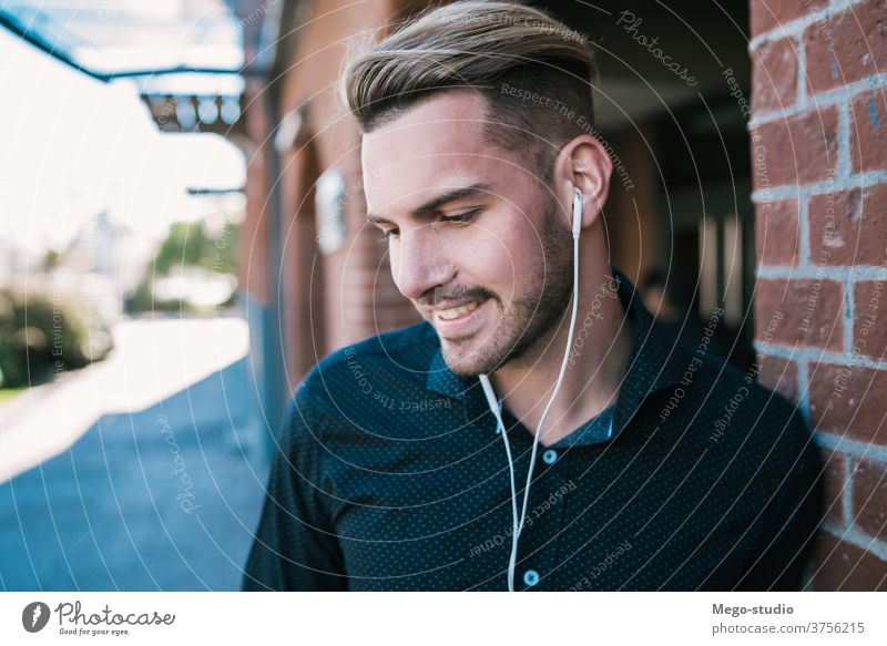 Man listening to music with earphones. person young people adult gadget outdoor technology lifestyle male casual alone sound entertainment city activity