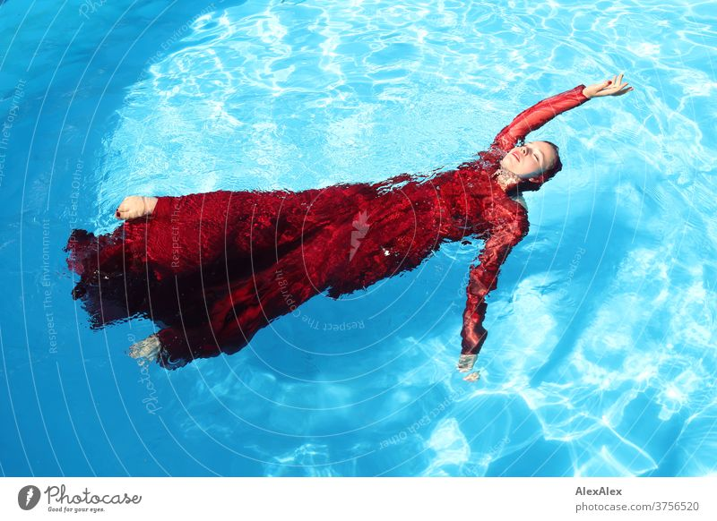 Young woman in a red ball gown lies with outstretched arm in a swimming pool Woman girl already daintily Athletic be afloat Sunlight Summer swimming pools Water