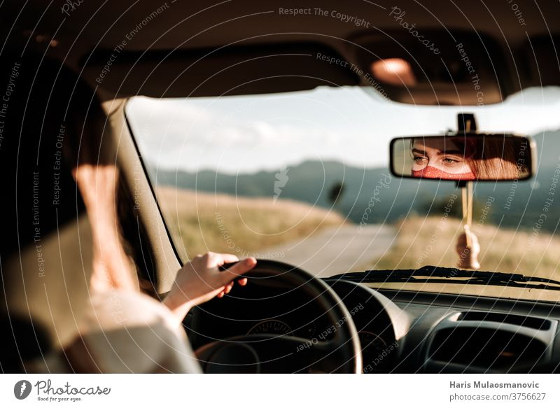 Woman with mask driving a car, face in review mirror , traveling in covid-19 time adventure auto automobile coronavirus drive driver face mask hand in the car