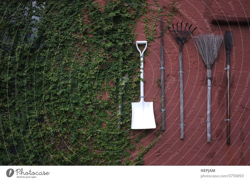 The gardening tools hanging on red cement wall. aged agriculture ancient background design dirty equipment farm farmer farming fork grass green group grunge