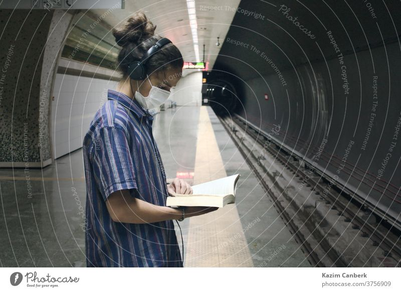 Masked teenager with headphone reading book while waiting for the subway to come metro underground man young student millennial university college adult mask