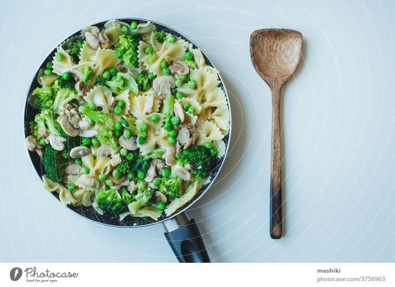 pan with cooked tasty italian vegetarian pasta with broccoli, green beans, mushrooms in creamy sauce. Tasty lunch or dinner food vegetable meal plate healthy