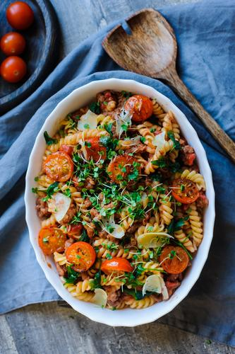 cooking tasty comfort food - italian fusilli pasta baked with meat sauce, cherry tomatoes and cheese lunch dinner plate dish vegetable basil cuisine red cooked